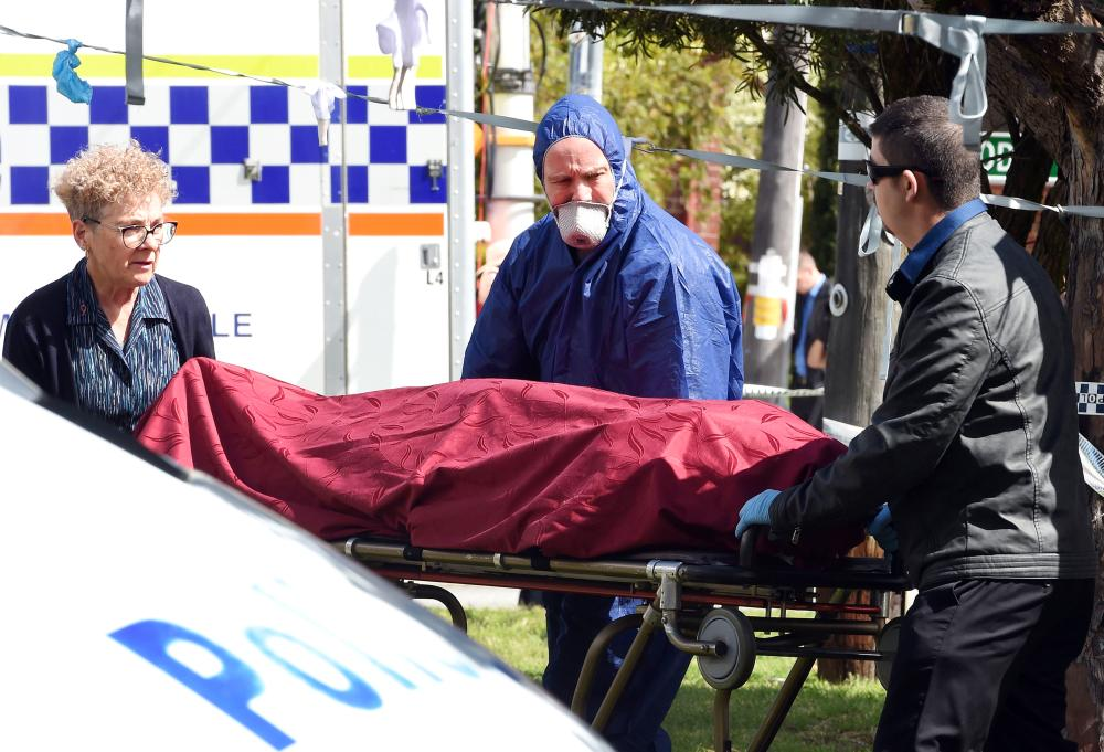 Forensic police and other officials remove a dead body from the crime site in the suburb of Australia's western city of Perth on Monday. — AFP