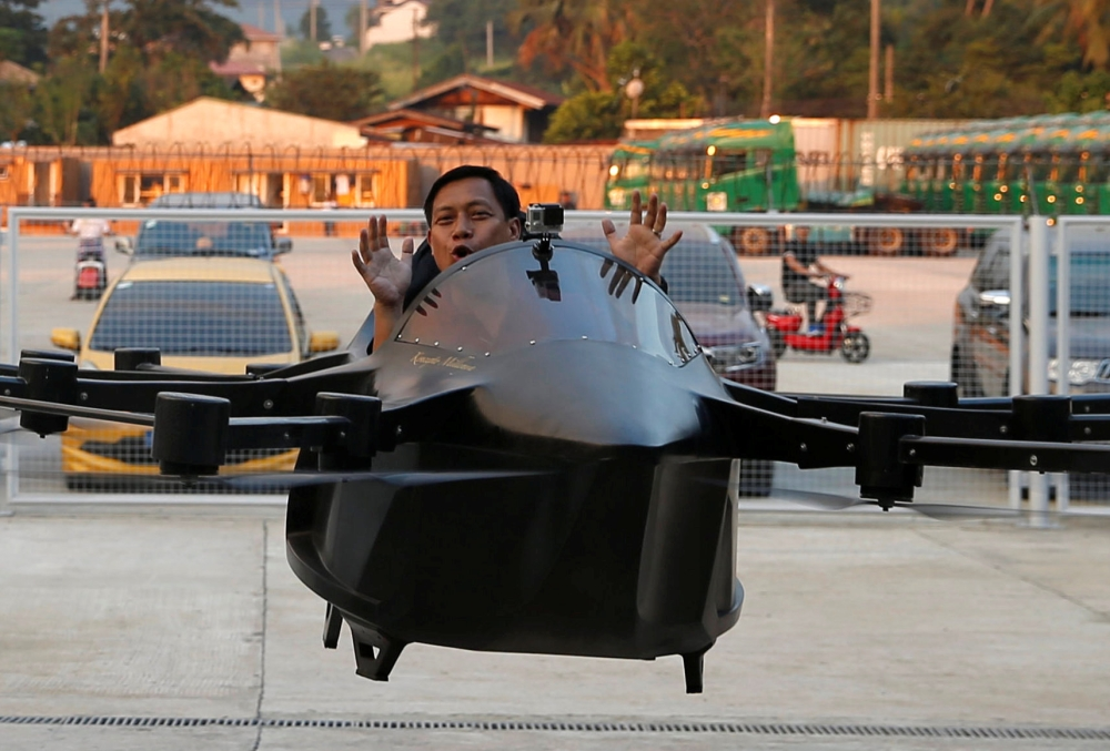 A journalist rides a drone flying car controlled by its inventor Kyxz Mendiola during its launch in the province of Batangas, Philippines, in this Sept. 23, 2018 file photo. — Reuters