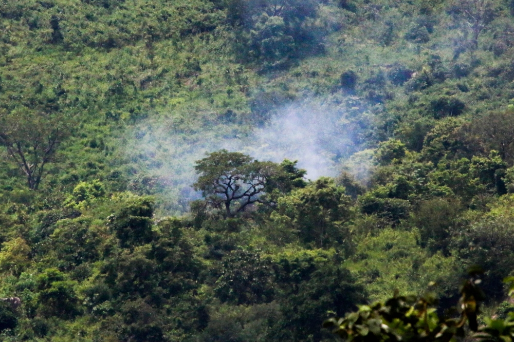 Smoke billows from trees after two Nigerian Air Force fighter jets taking part in rehearsals ahead of the nation's Independence Day anniversary crashed on Katampe Hills, on the outskirts of Abuja, on Friday. — AFP