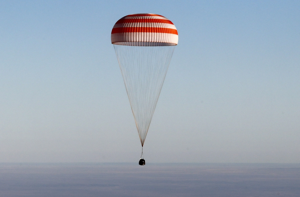 The Soyuz MS-08 capsule carrying the crew of Drew Feustel and Ricky Arnold of the US, and Oleg Artemyev of Russia, descends beneath a parachute just before landing in a remote area outside the town of Dzhezkazgan (Zhezkazgan), Kazakhstan, on Thursday. — Reuters