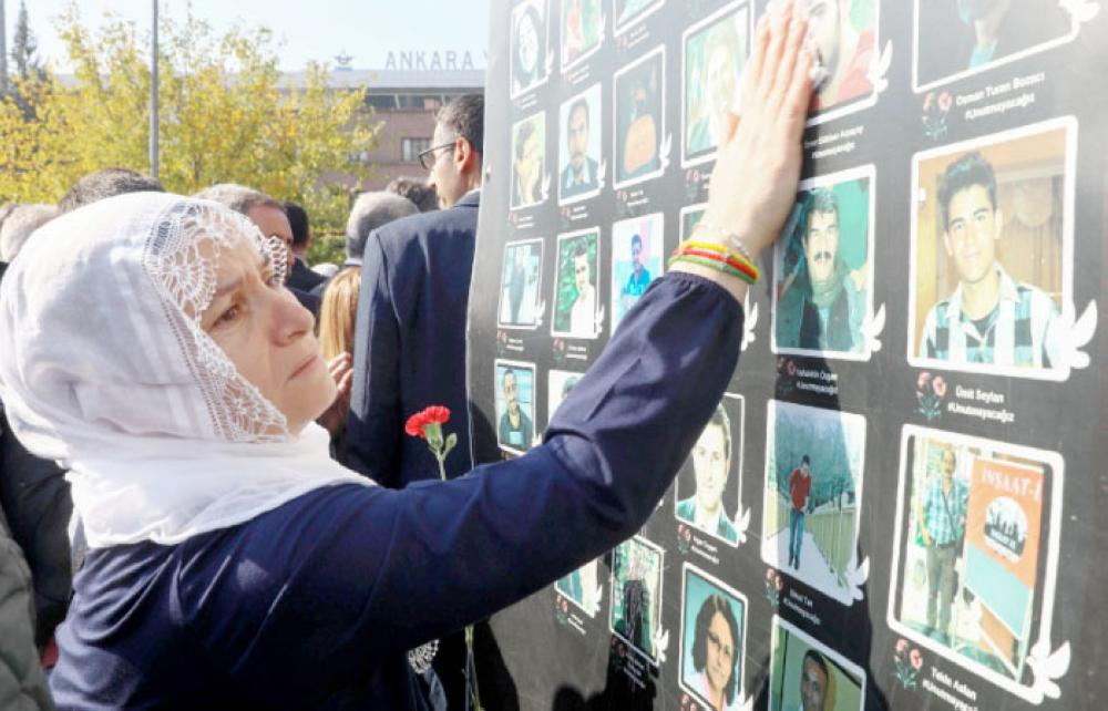 A woman stands in front of photographs of suicide attack victims, during a demonstration in Ankara, on Wednesday, which was held to mark the third anniversary of twin suicide attacks on October 10, 2015 which took place in the Turkish capital. — AFP