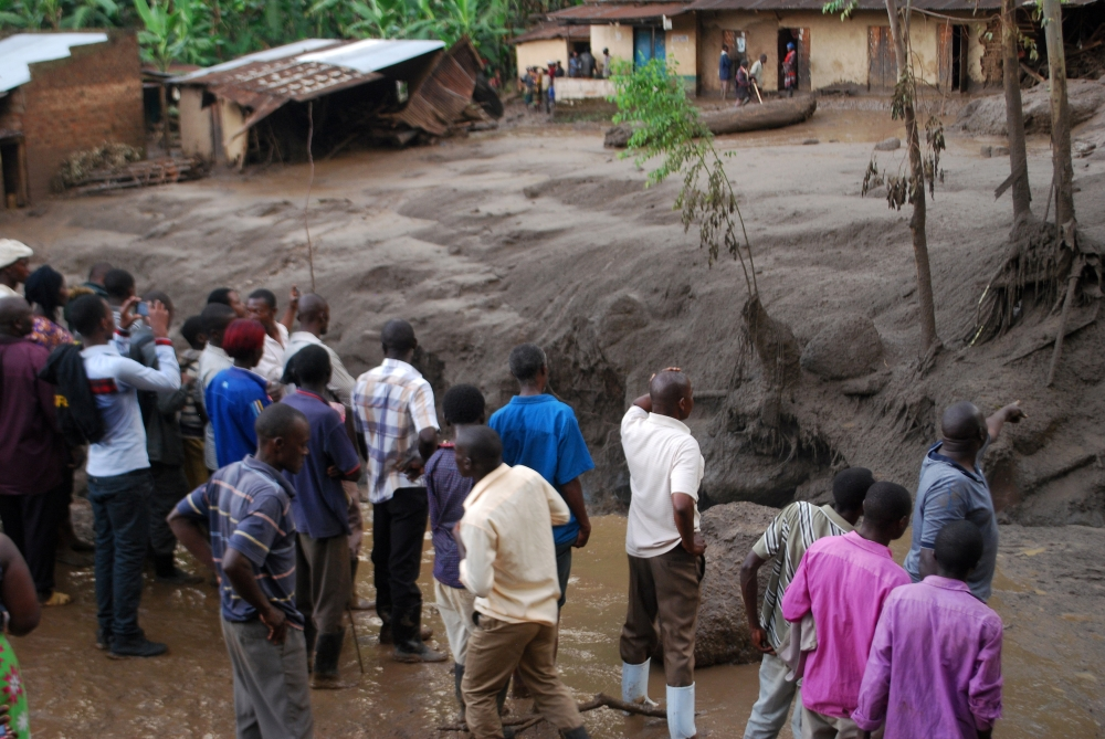 Survivors look at the aftermath as flood waters pass through destroyed homes, after a landslide rolled down the slopes of Mt. Elgon through their village in Bududa district, Uganda, on Friday. — Reuters