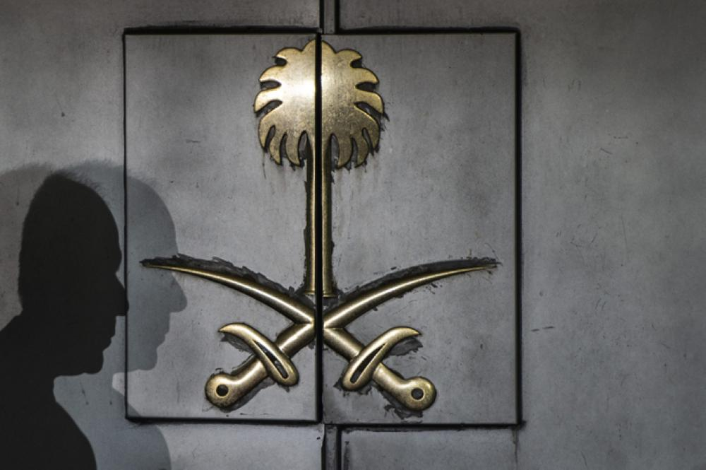 The shadow of a security guard is seen on the entrance door of the Saudi Arabia's consulate in Istanbul, Turkey, on Friday. — AFP