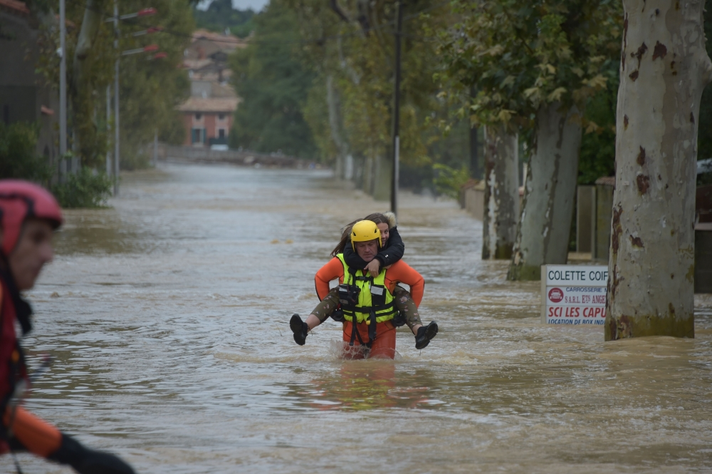 A firefighter helps a youngster in a flooded street during rescue operation following heavy rains that saw rivers bursting banks in Trebes, near Carcassone, southern France, on Monday. — AFP