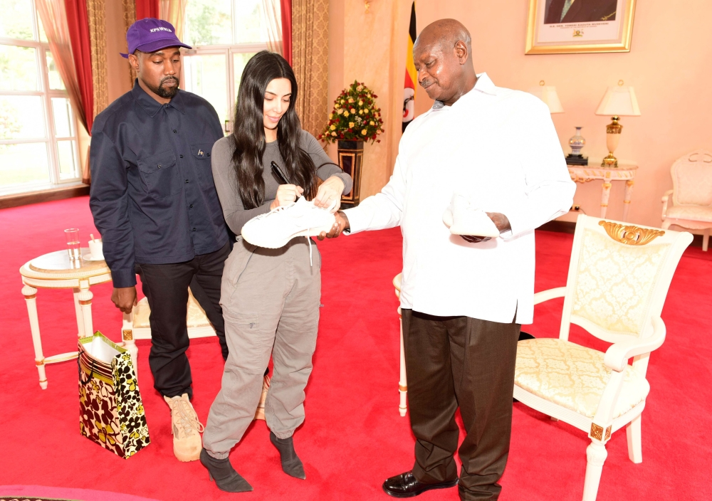 A handout photo shows Uganda's President Yoweri Museveni (R) meeting with US rapper Kanye West (L) and his wife Kim Kardashian at the State House in Entebbe, Uganda.  — AFP