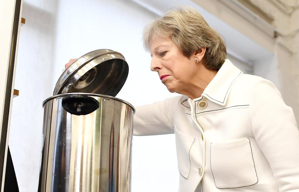 Britain's Prime Minister Theresa May peers into a hot water urn as she helps make drinks during a visit to social group in Vauxhall, south London, on Monday. — AFP