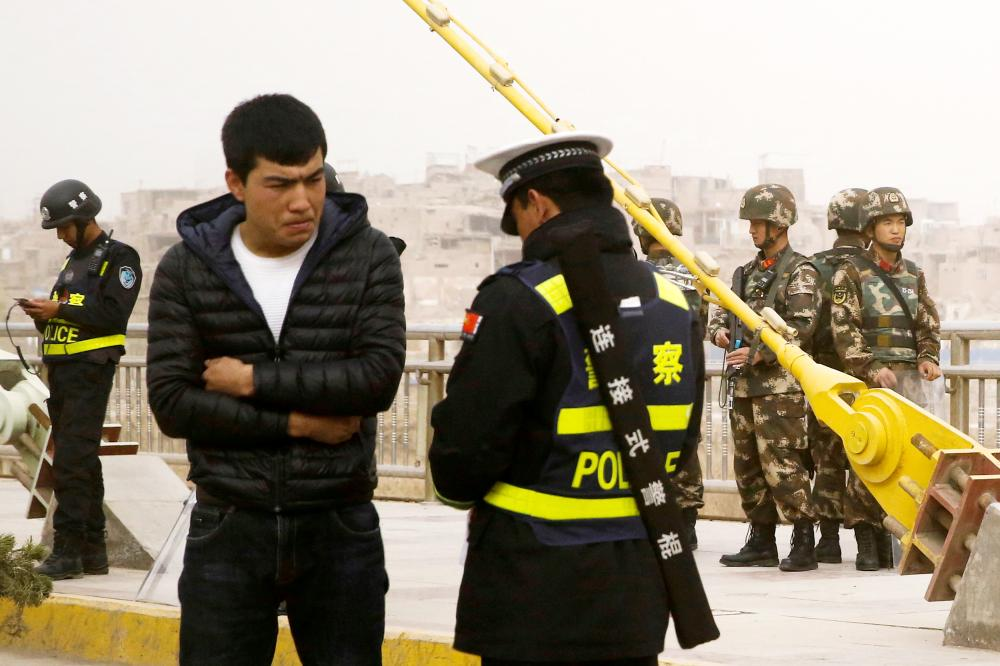 A police officer checks the identity card of a man as security forces keep watch in a street in Kashgar, Xinjiang Uighur Autonomous Region, China, in this March 24, 2017 file photo. — Reuters
