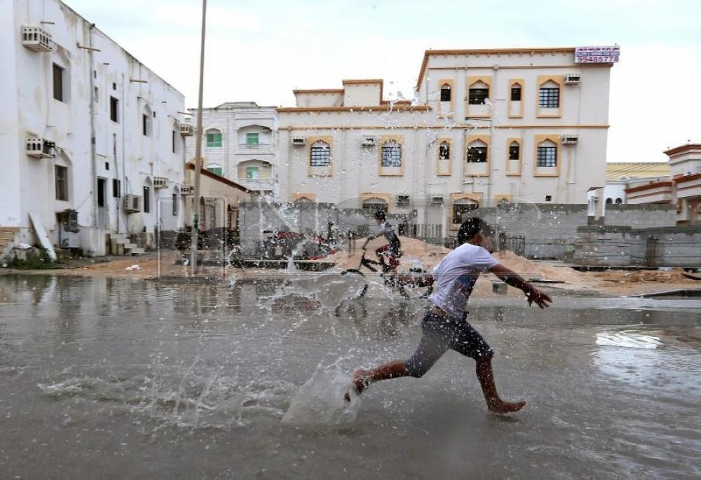 Children from a local neighborhood play in a roadside puddle accumulated from rain brought by Cyclone Luban in Salalah, Oman. — Reuters