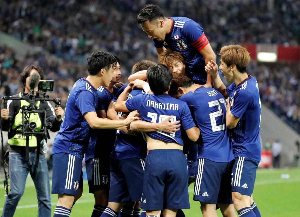 Japan's Takumi Minamino celebrates scoring their first goal with teammates against Uruguay during their friendly at Saitama Stadium Tuesday. — Reuters