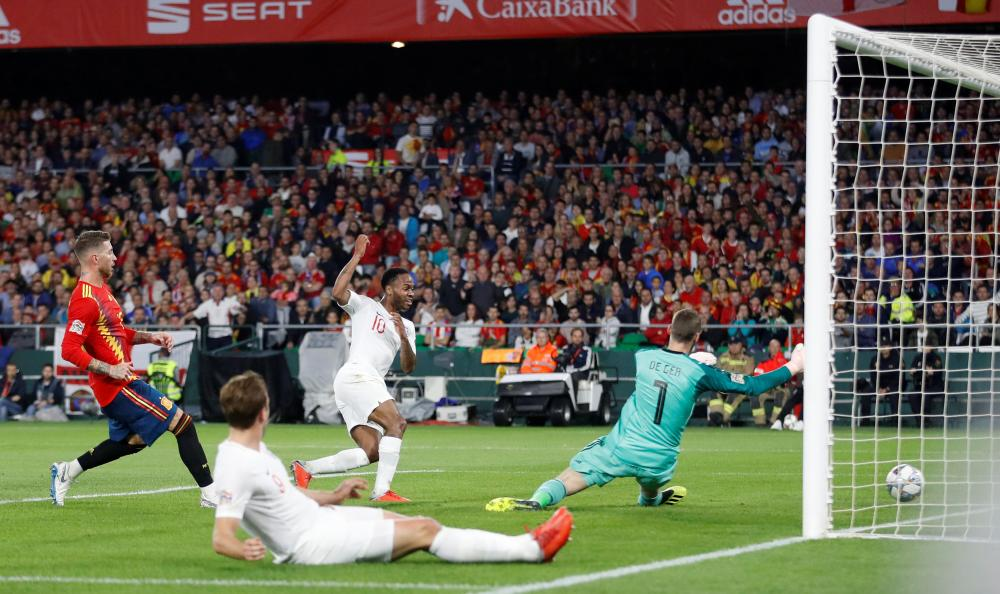 England's Raheem Sterling scores their third goal past Spain's goalkeeper David De Gea during the UEFA Nations League Championship at Estadio Benito Villamarin in Seville Monday. — Reuters