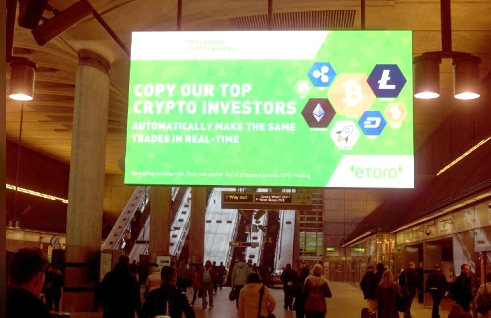 Giant electronic billboards display adverts for crypto currency investment companies as commuters arrive at Canary Wharf tube station in London, Britain, in this file photo. — Reuters