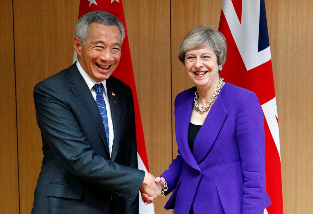 Singapore's Prime Minister Lee Hsien Loong poses with Britain's counterpart Theresa May at the ASEM leaders summit in Brussels, Belgium on Thursday. — Reuters