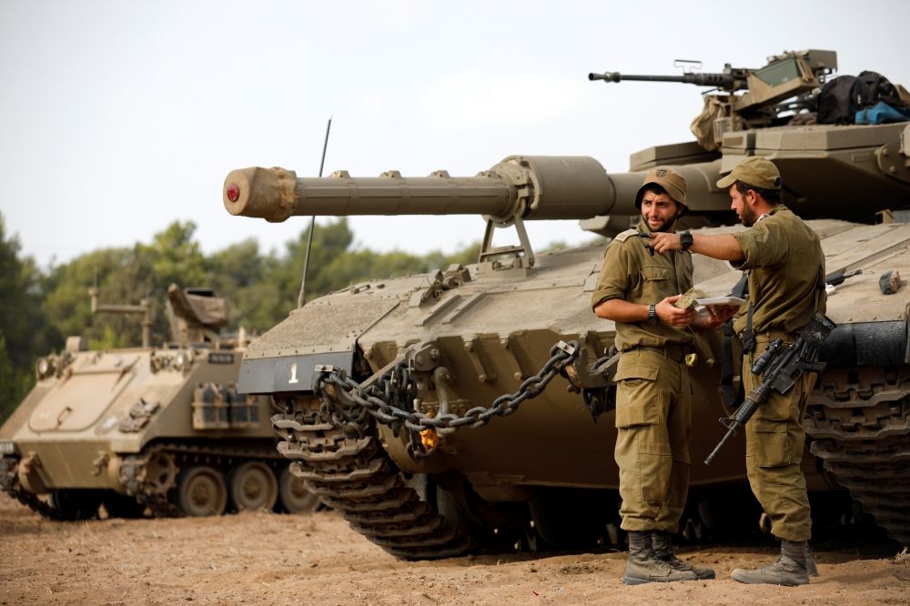 Israeli soldiers speak next to a tank as military armored vehicles gather in an open area near Israel's border with the Gaza Strip on Thursday. — Reuters