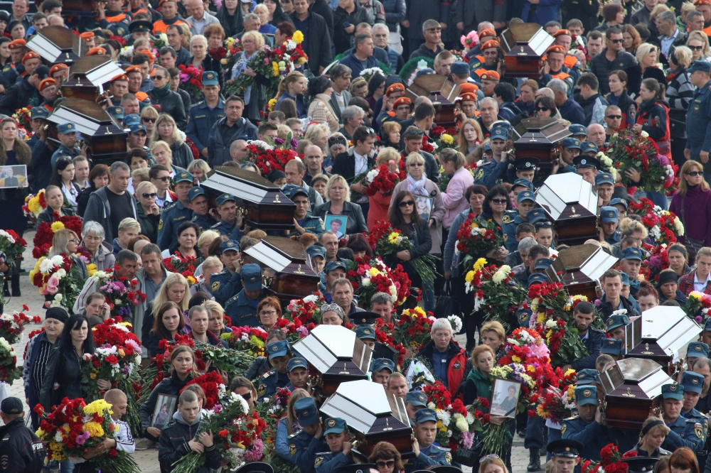 People attend a memorial ceremony before the funeral of victims of an attack on a local college in the city of Kerch, Crimea, on Friday. — Reuters