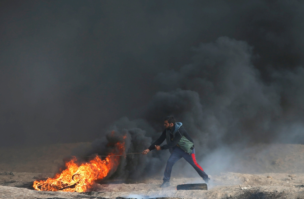 A Palestinian demonstrator moves a burning tire during a protest calling for lifting the Israeli blockade on Gaza and demanding the right to return to their homeland, at the Israel-Gaza border fence in Gaza, on Friday. — Reuters