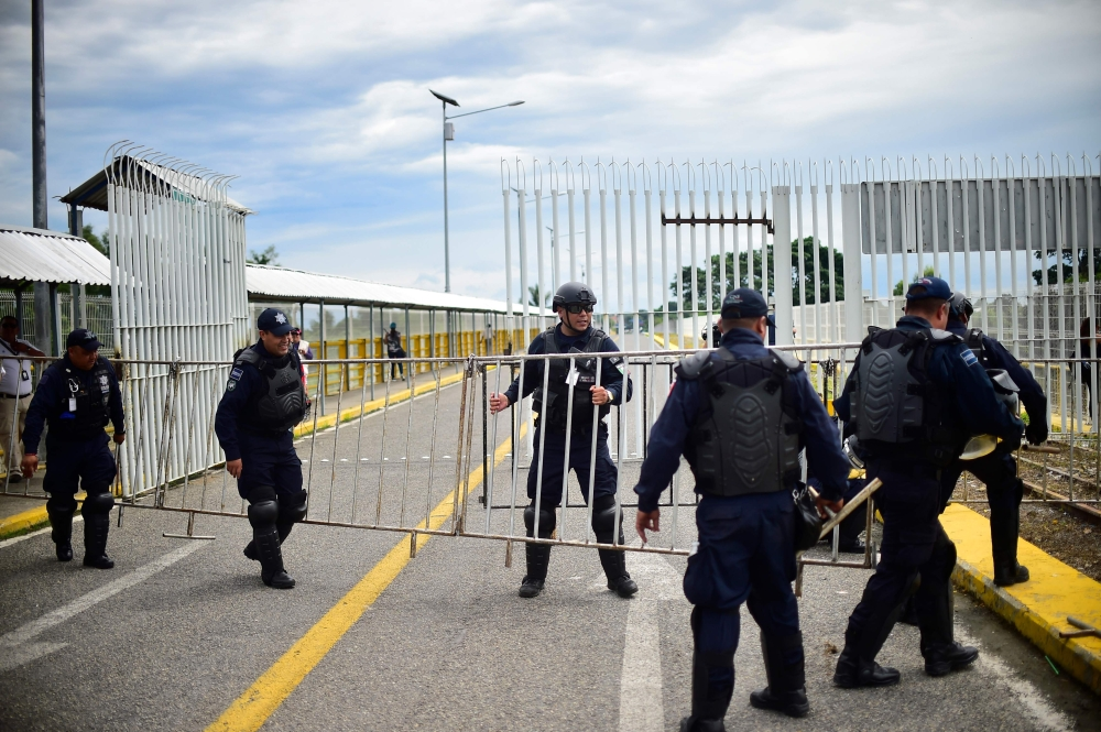 Mexican Federal Police officers get ready for the arrival of a caravan of Honduran migrants heading to the US, on the international bridge in Ciudad Hidalgo, Chiapas state, Mexico, in the border with Guatemala, on Friday. — AFP