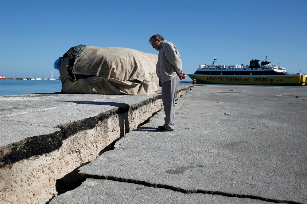A man looks at the damaged pier of the port of Zakynthos, following an earthquake off the Zakynthos Island, Greece, on Friday. — Reuters