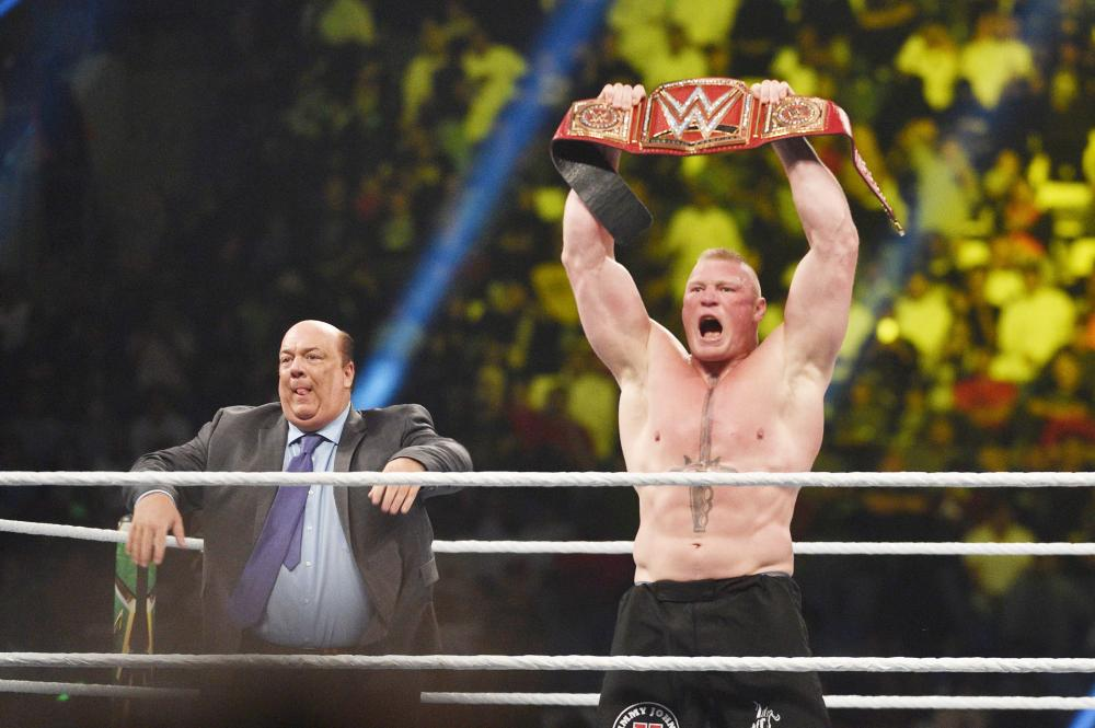 Brock Lesnar celebrates, with his manager Paul Heyman, after winning the WWE Universal Championship match at WWE Crown Jewel show at the King Saud University Stadium in Riyadh Friday. — AFP