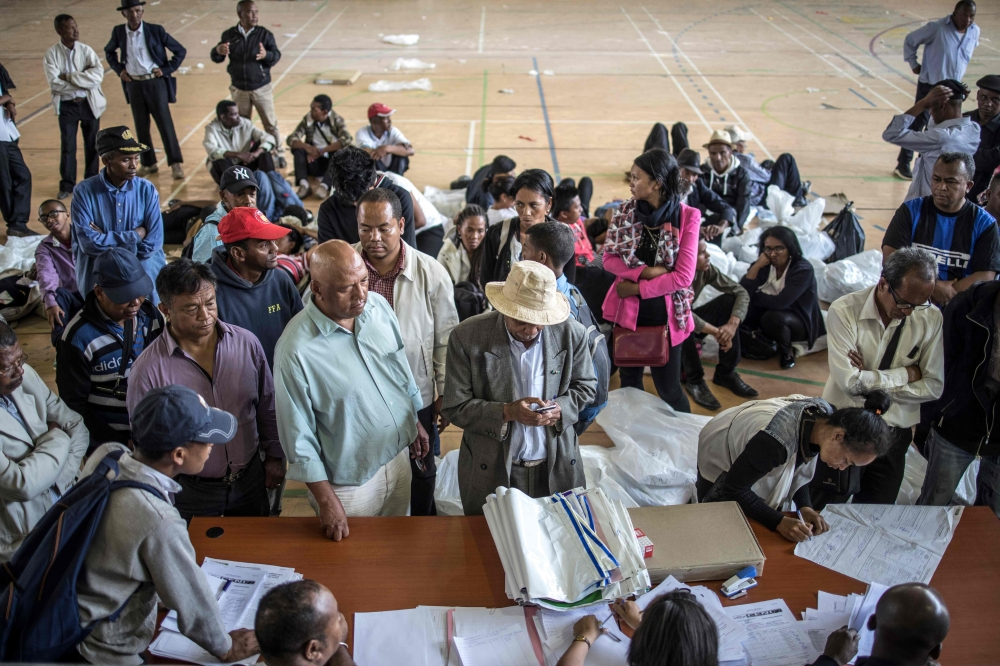 Delegates are seen handing over election reports at the Stade Municipal de Mahamasina Antananarivo on Thursday where the national tallying center has been set up, at the end of the first round of the presidential elections. — AFP