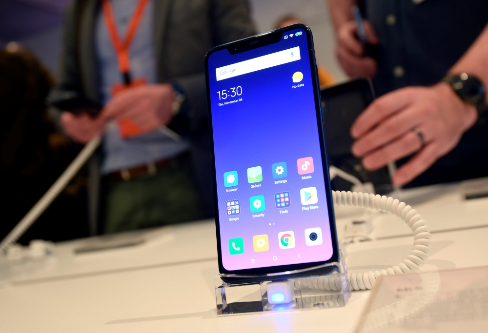 Guests view the Xiaomi Mi 8 smartphone at a UK launch event in London, Britain, on Thursday. — Reuters
