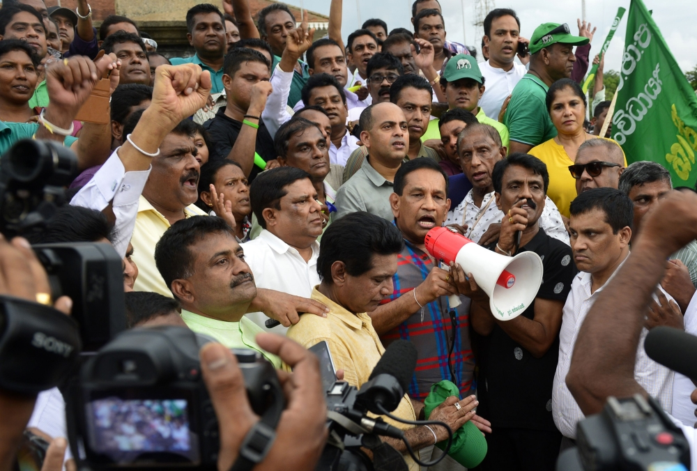 Sri Lankan politician Rajitha Senaratne, center, addresses a rally of supporters of deposed prime minister Ranil Wickremesinghe in the capital Colombo on Thursday to protest against the actions of President Maithripala Sirisena. — AFP