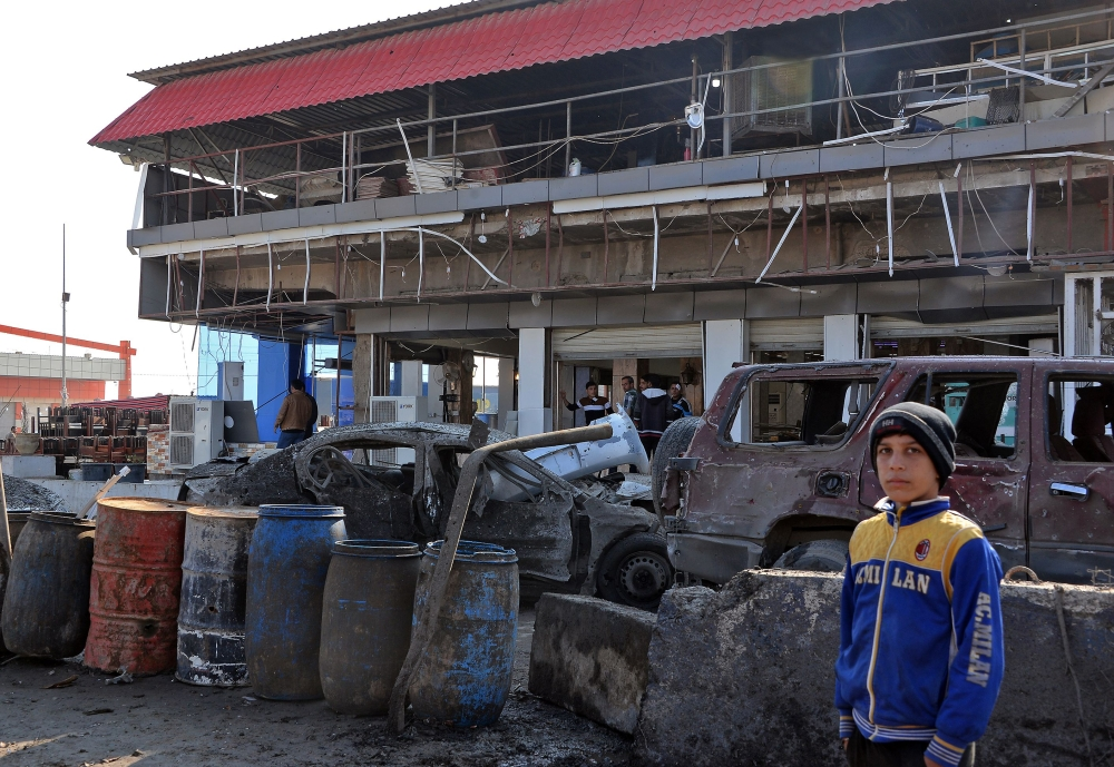 An Iraqi boy stands near a restaurant on Friday at the scene of a car bomb explosion that killed three people and wounded a dozen in Mosul on Thursday. — AFP