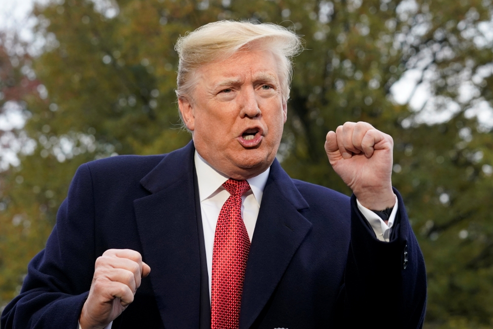 US President Donald Trump speaks to reporters as he departs the White House en route to Paris from Washington on Friday. — Reuters