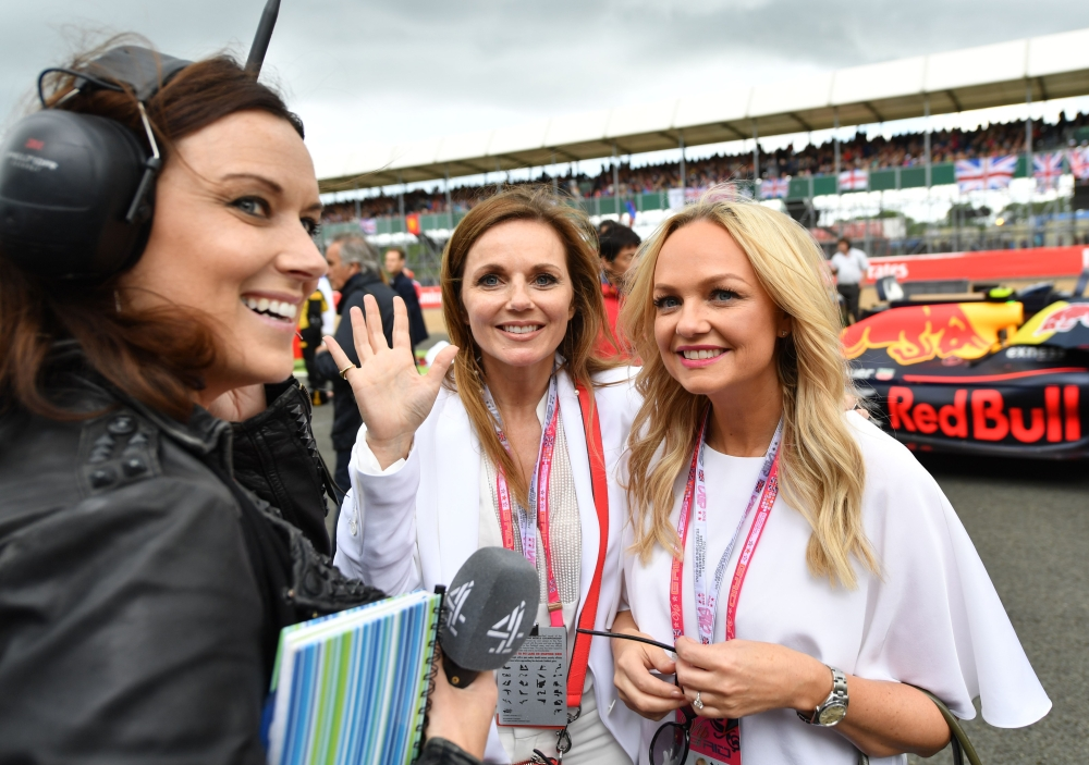 In this file photo taken on July 10, 2016, former singers from the British Band the Spice Girls, Geri Halliwell (C), and Emma Bunton (R) pose for a photograph as they stand with the Infiniti Red Bull racing team on the track ahead of the British Formula One Grand Prix at Silverstone motor racing circuit in Silverstone, central England. — AFP