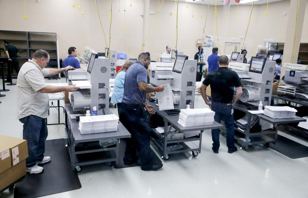 Elections staff load ballots into machines as recounting begins at the Broward County Supervisor of Elections Office in Lauderhill, Florida, on Sunday. — AFP