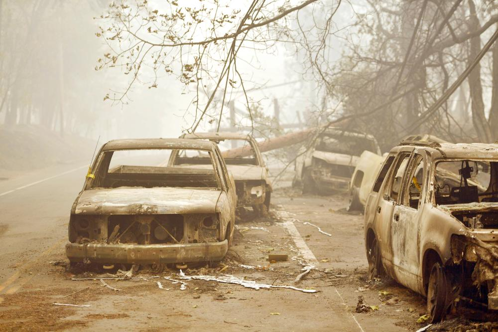 Burned out vehicles are seen on the side of the road in Paradise, California, after the Camp fire tore through the area on Saturday.  — AFP