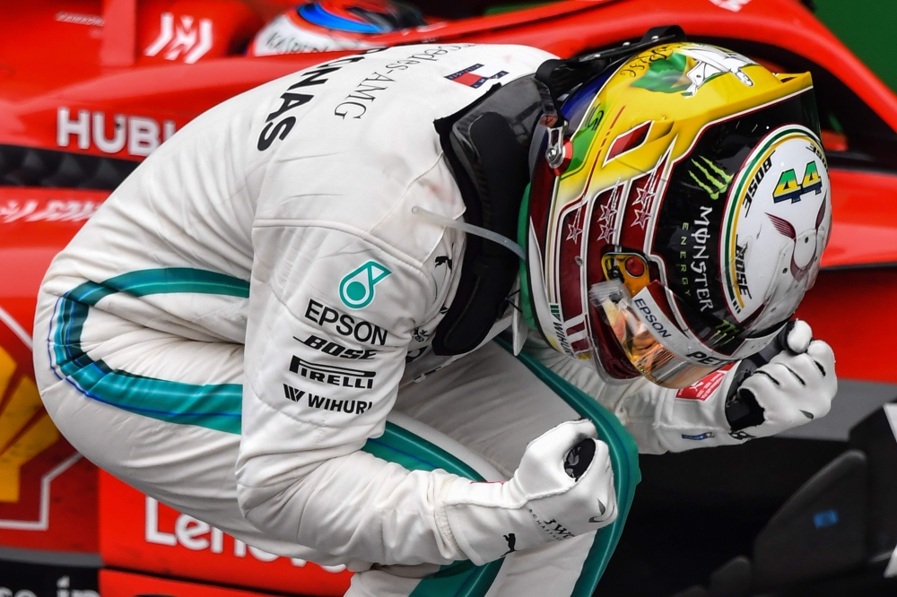 Mercedes' British driver Lewis Hamilton celebrates after winning the F1 Brazil Grand Prix, while Mercedes took the constructors title, at the Interlagos racetrack in Sao Paulo, Brazil on Sunday. Max Verstappen in a Red Bull was second with Ferrari's Kimi Raikkonen in third. — AFP