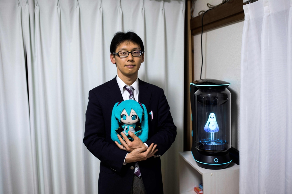 Japanese Akihiko Kondo poses next to a hologram of Japanese virtual reality singer Hatsune Miku as he holds the doll version of her at his apartment in Tokyo, a week after marrying her, in this Nov. 10, 2018 file photo. — AFP