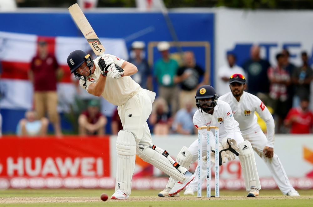 England's Jos Buttler (L) plays a shot next to Sri Lanka's wicketkeeper Niroshan Dickwella during the first cricket Test at Galle, Sri Lanka, recently. Reuters