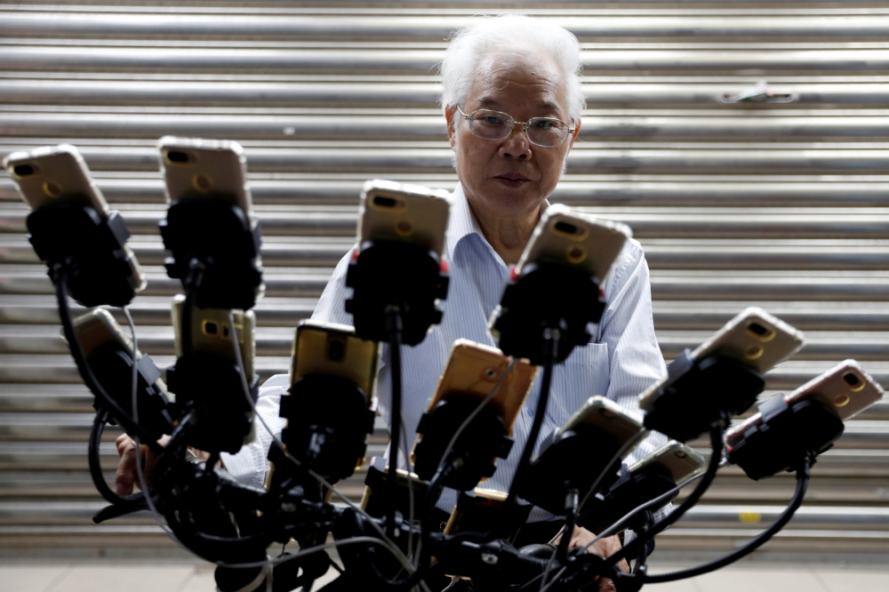 Taiwanese Chen San-yuan, 70, known as 'Pokemon grandpa', rides his bicycle as he playing mobile game 'Pokemon Go' by Nintendo, near his home with 15 mobile phones, in New Taipei City, Taiwan. — Reuters