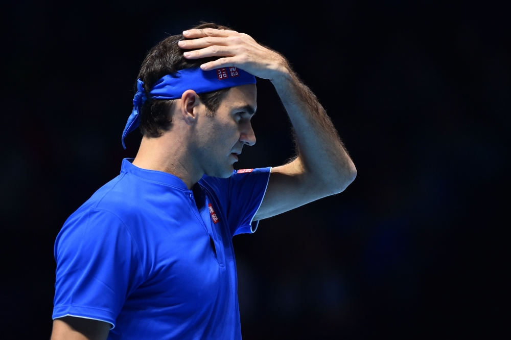 Switzerland's Roger Federer reacts while playing Japan's Kei Nishikori during their singles round robin match on day one of the ATP World Tour Finals tennis tournament at the O2 Arena in London on Sunday.  — AFP