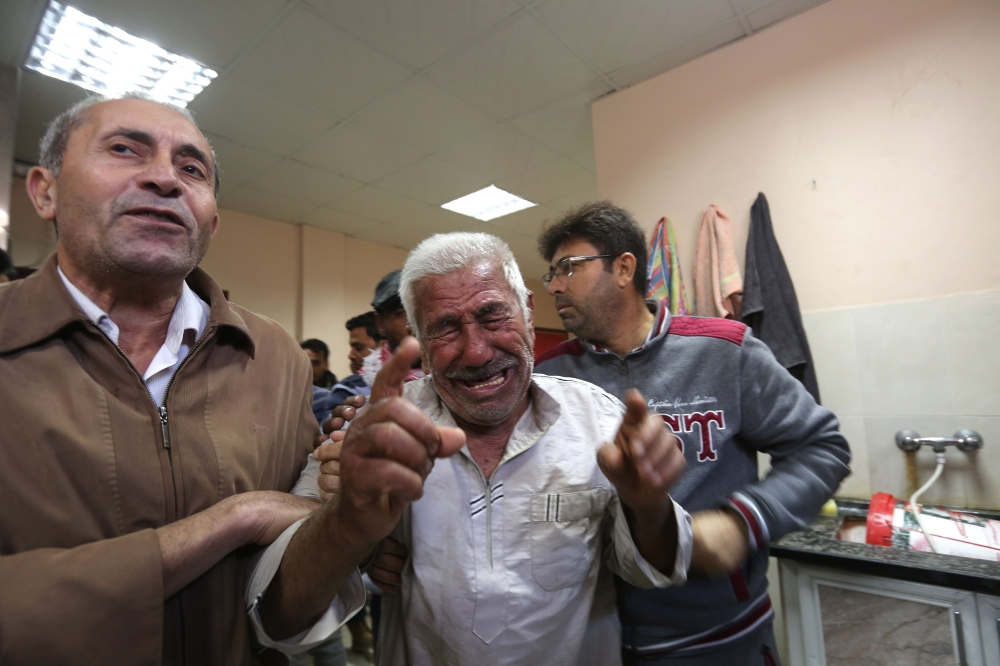 The relative of a man killed in an Israeli air strike across the Gaza Strip reacts after identifying his body at a hospital morgue in Beit Lahya on Tuesday. — AFP
