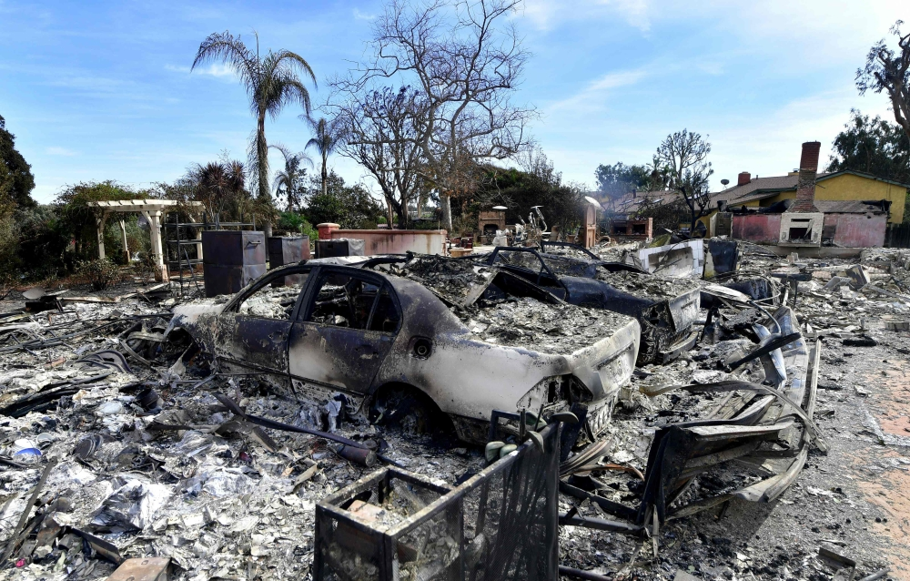 The remains of burned down homes and vehicles resulting from the Woolsey Fire are seen on Busch Drive in Malibu, California, on Tuesday. — AFP