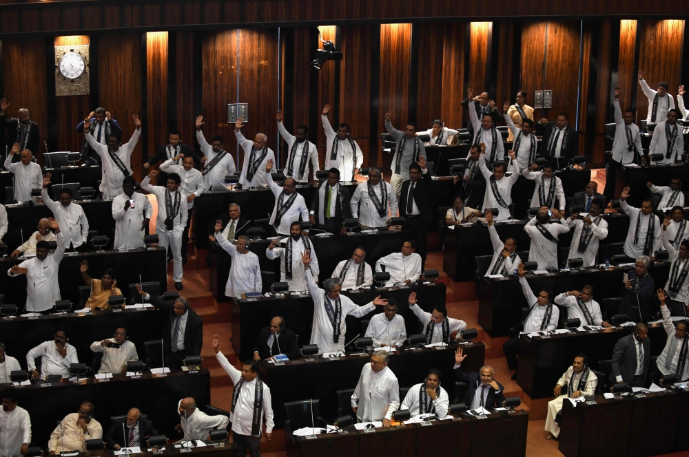 Members of the Sri Lankan parliament raise their hands at a session in Colombo on Wednesday. — AFP