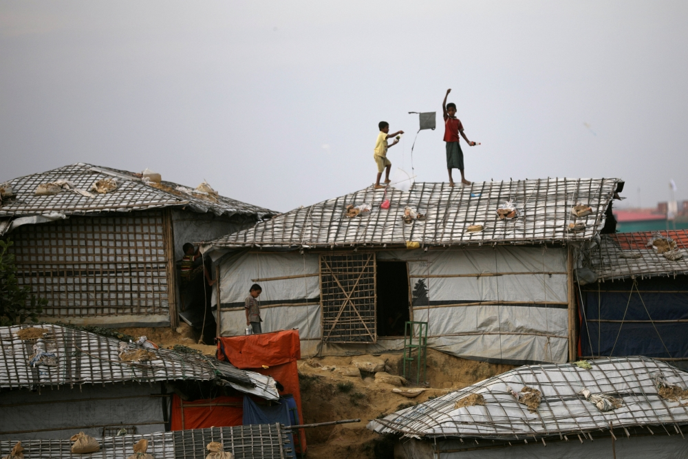 Rohingya refugee children fly kites on top of their shelter at Balikhali camp in Cox's Bazar, Bangladesh, on Wednesday. — Reuters