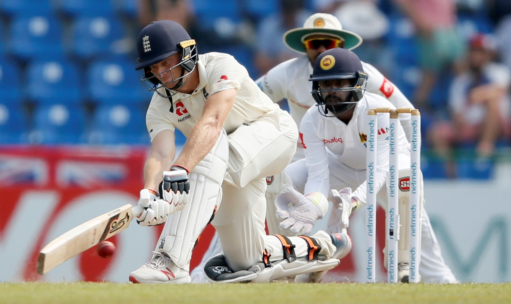 England's Jos Buttler plays a shot next to Sri Lanka's wicketkeeper Niroshan Dickwella on the first day of the second cricket Test at Pallekele, Sri Lanka, on Wednesday. — Reuters