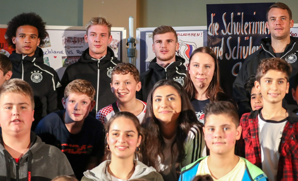 (L-R) Germany's midfielder Leroy Sane, Germany's forward Julian Brandt, Germany's goalkeeper Manuel Neuer and Germany's forward Timo Werner pose for a group photo with students of the sport high school after a question and answer session in Leipzig, eastern Germany on Tuesday, two days before an international friendly match Germany vs Russia. — AFP