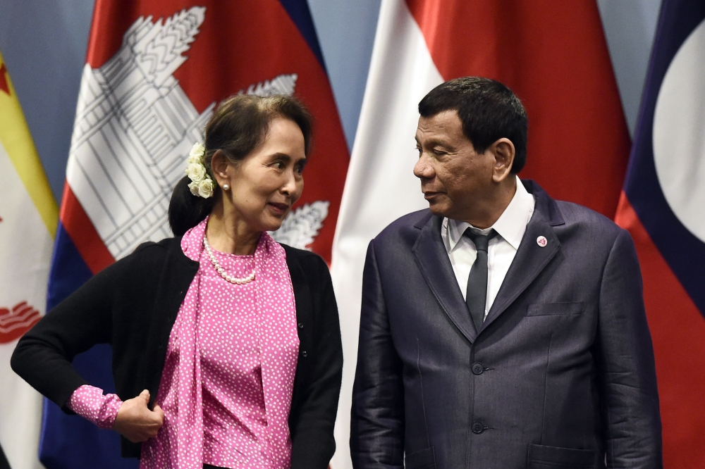 Philippine President Rodrigo Duterte, right, listens to Myanmar State Counselor Aung San Suu Kyi as they arrive on stage to pose for a group photo before the start of the ASEAN-Japan summit on the sidelines of the 33rd Association of Southeast Asian Nations (ASEAN) summit in Singapore on Wednesday. — AFP