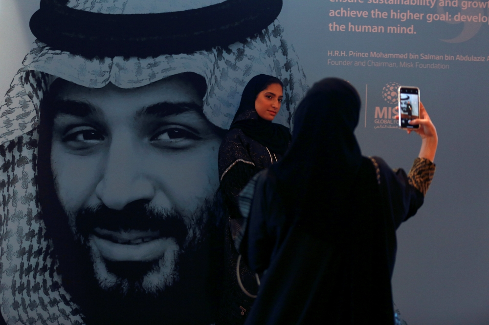 Participants take photos next to a picture of Crown Prince Muhammed Bin Salman, deputy premier and minister of defense, during the Misk Global Forum in Riyadh on Wednesday. — Reuters
