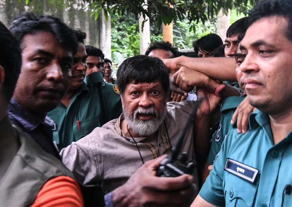 Activist and photographer Shahidul Alam arrives surrounded by policemen for an appearance in court in Dhaka in this Aug. 6, 2018 file photo. — AFP
