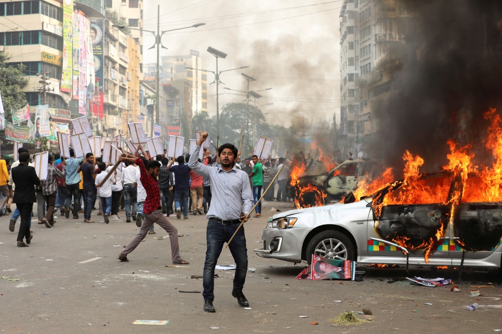Bangladesh Nationalist Party activists set fire to a police vehicle during clashes in Dhaka on Wednesday. — Reuters
