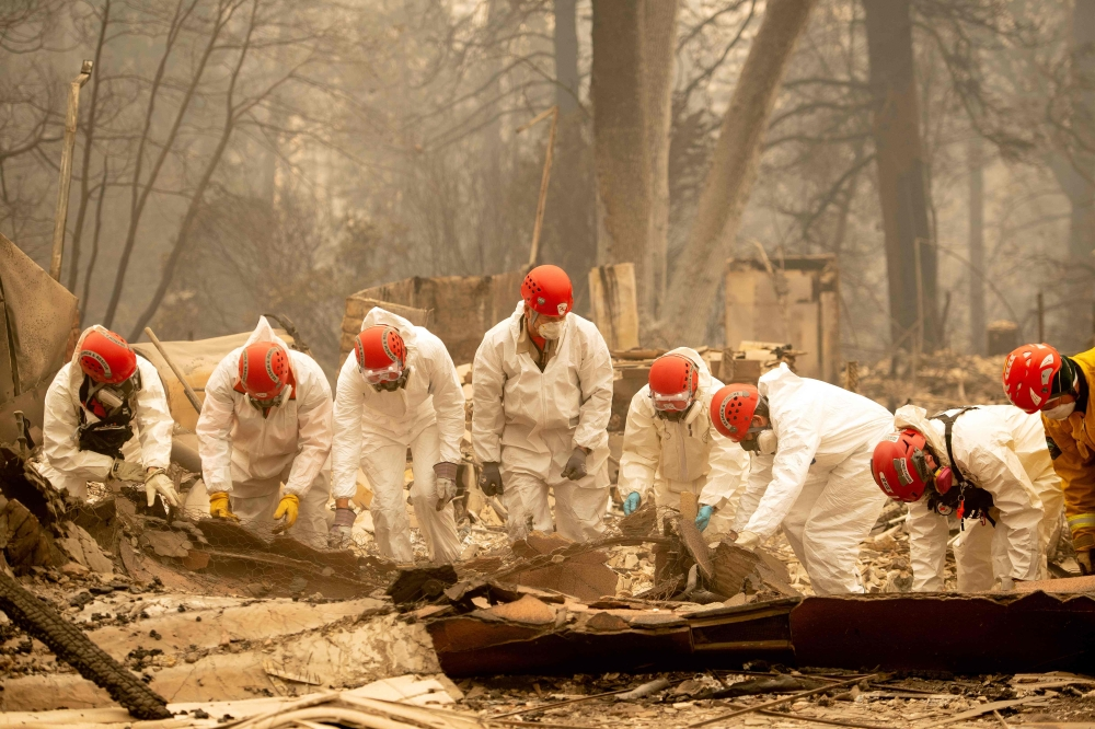 Rescue workers sift through rubble in search of human remains at a burned property in Paradise, California, on Wednesday. — AFP