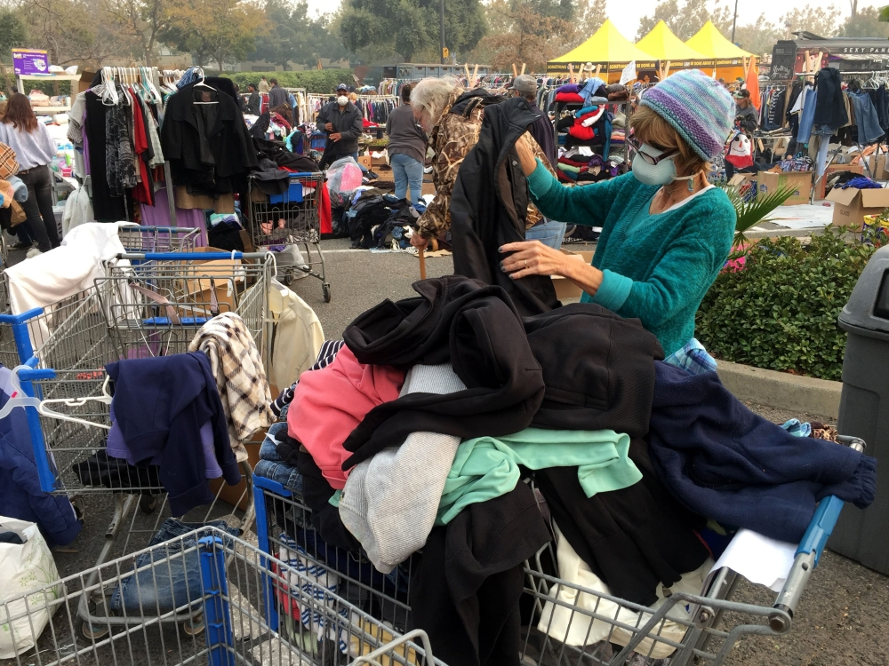 Volunteer Cathryn Flores classifies clothes at a donation fair for fire evacuees camping at a parking lot in Chico, California, on Wednesday. — AFP