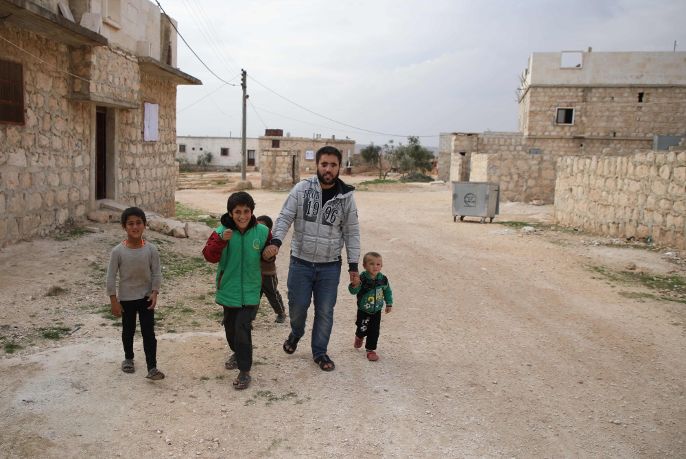 Ahmad Talha, a former Syrian rebel fighter who lost his sight as a result of a gunshot wound, walks with his son, right, and children in the rebel-controlled town of Anjara, in the western Aleppo countryside, in this Nov. 10, 2018 file photo. — AFP