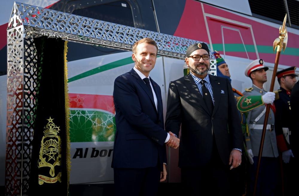 French President Emmanuel Macron, left, and Moroccan King Mohammed VI shake hands as they inaugurate a high-speed line at Tangiers train station on Thursday. — AFP