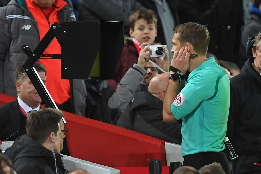 In this file photo, referee Craig Pawson looks at the pitch-side screen after speaking to the VAR (Video Assistant Referee) before giving Liverpool a penalty during the English FA Cup fourth round football match between Liverpool and West Bromwich Albion at Anfield in Liverpool, north west England. The Premier League is set to use the Video Assistant Referee system from next season after clubs